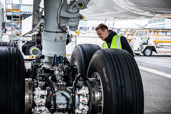 Man working on the wheel of an airplane.
